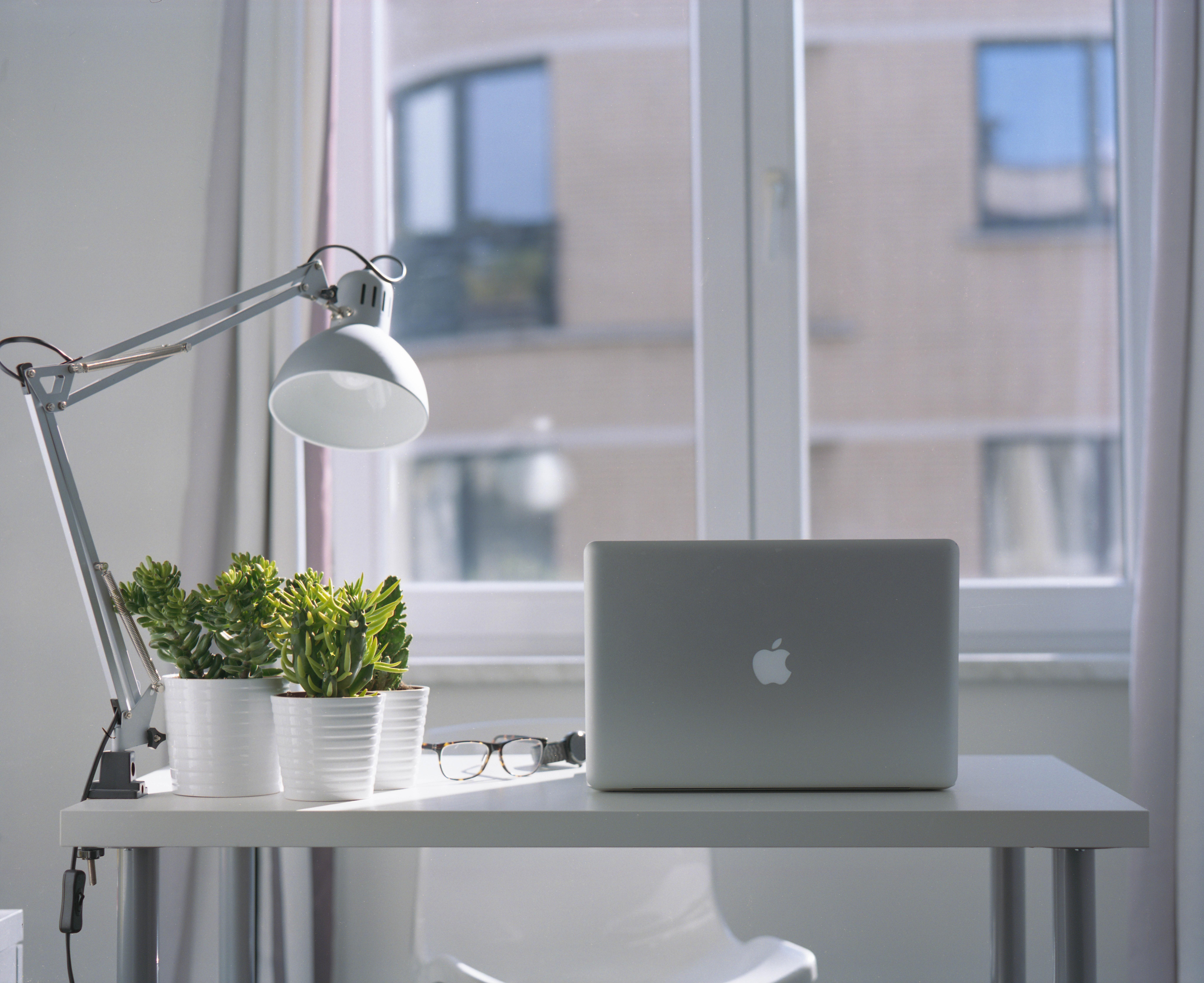 Skrivbord med dator framför fönster
